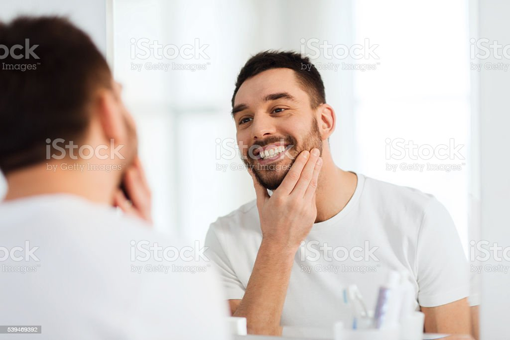 happy young man looking to mirror at home bathroom stock photo