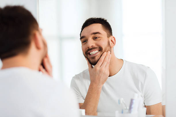 young man looking at mirror in bathroom pictures images and stock