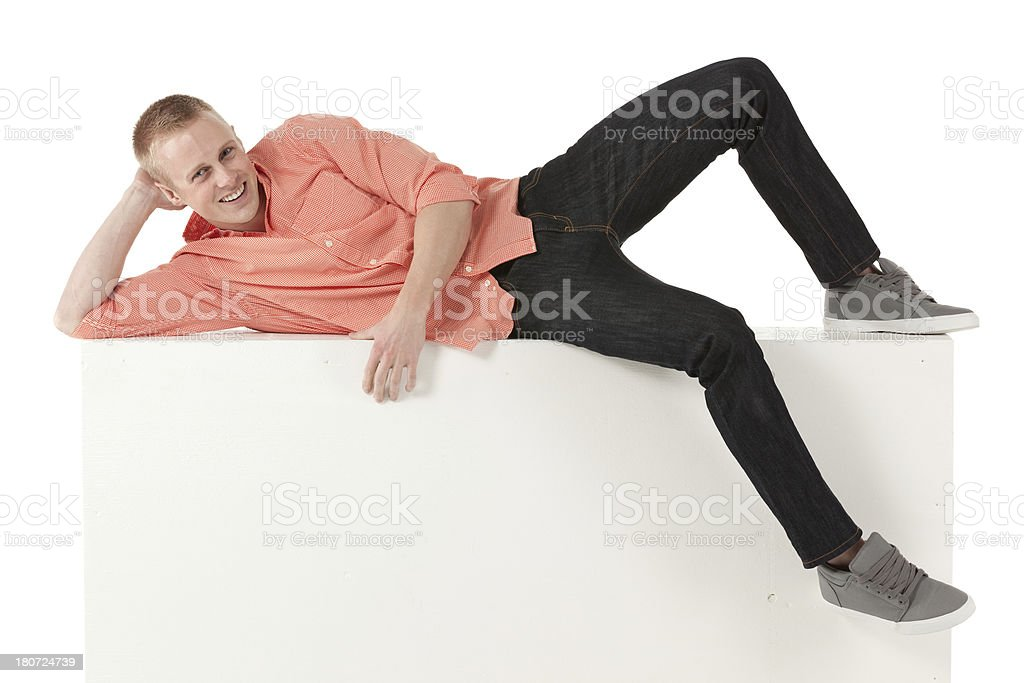 Happy young man lying on the ledge of a wall stock photo