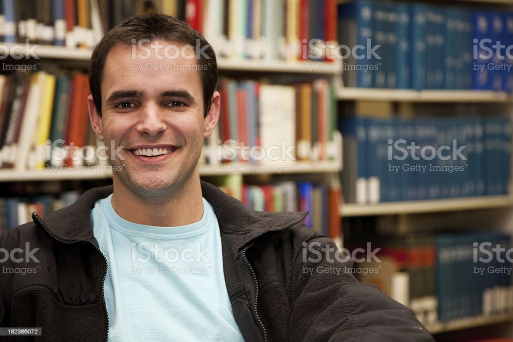 Happy Young Man Near Books in School Library royalty-free stock photo