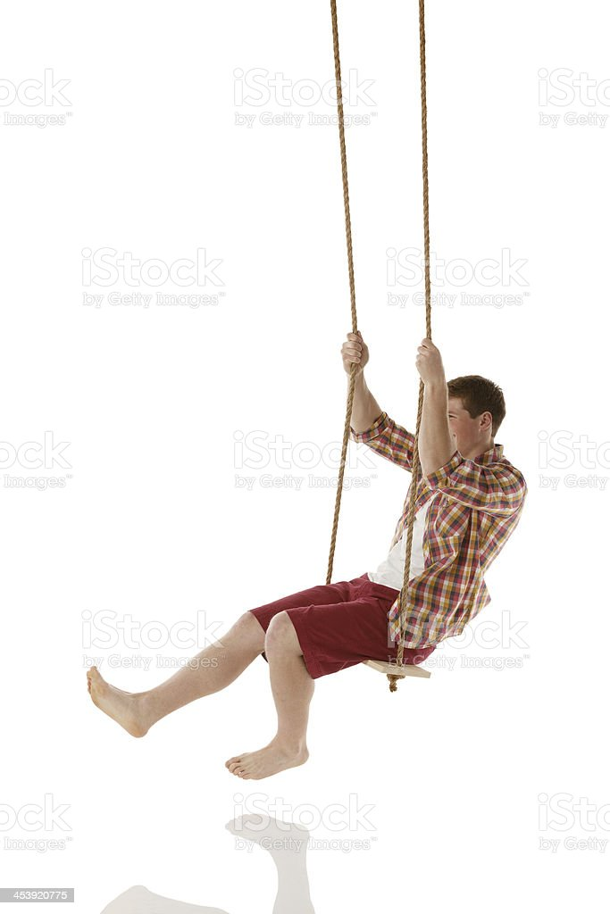 Happy young man on a rope swing royalty-free stock photo