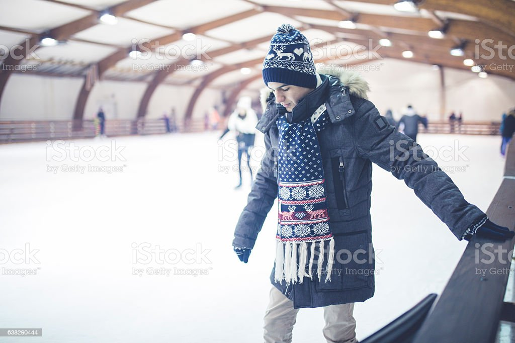 Happy young man on skating rink stock photo