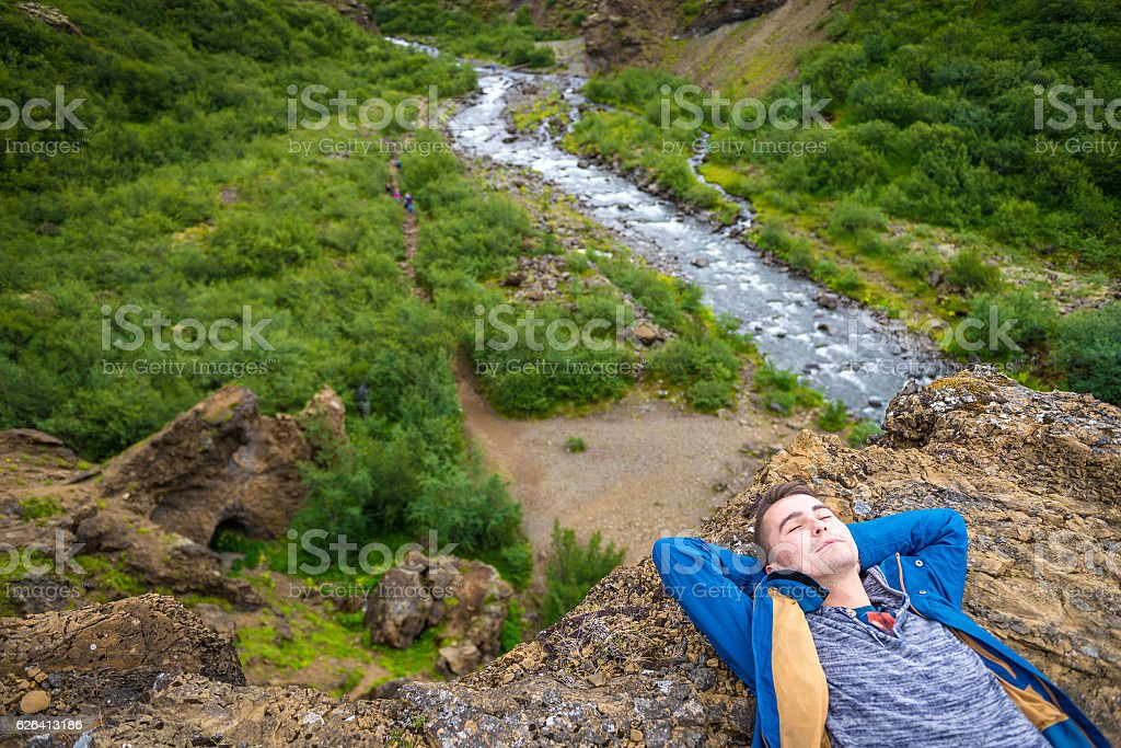 Happy young man on the edge of the cliff stock photo