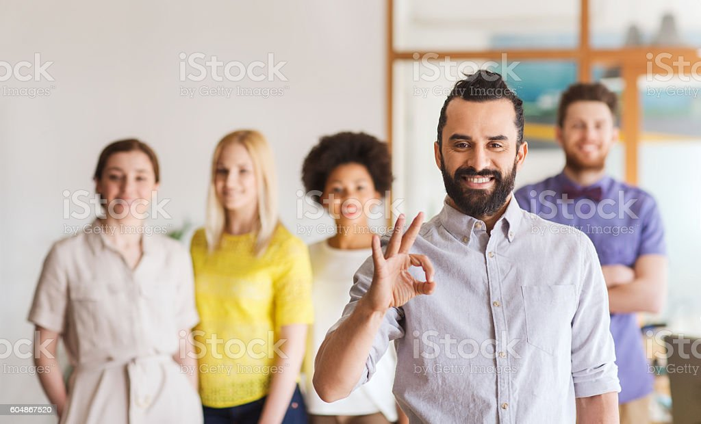 happy young man over creative team in office stock photo