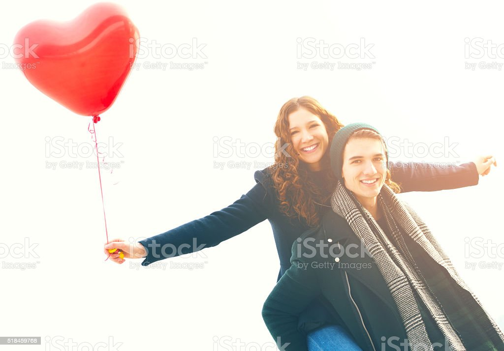 Happy young man piggybacking his girlfriend stock photo