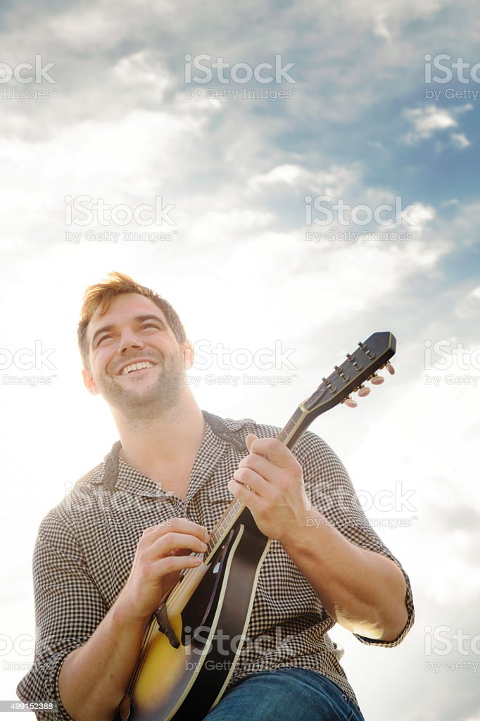 Happy young man playing the mandoline outdoors stock photo