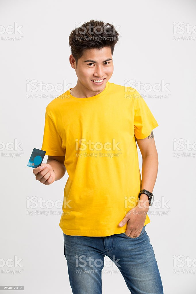 Happy young man posing with credit card stock photo