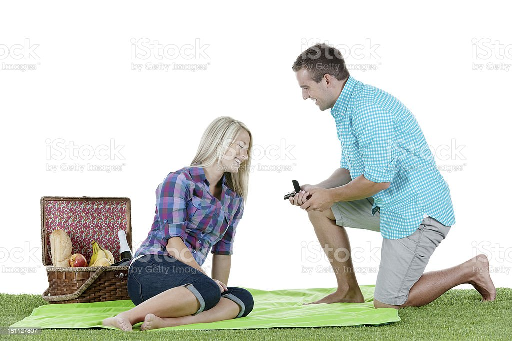Happy young man proposing to his girlfriend stock photo