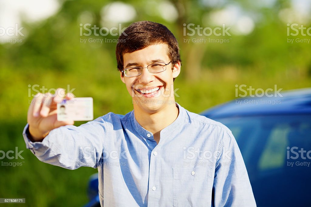 Happy young man showing his driving license stock photo