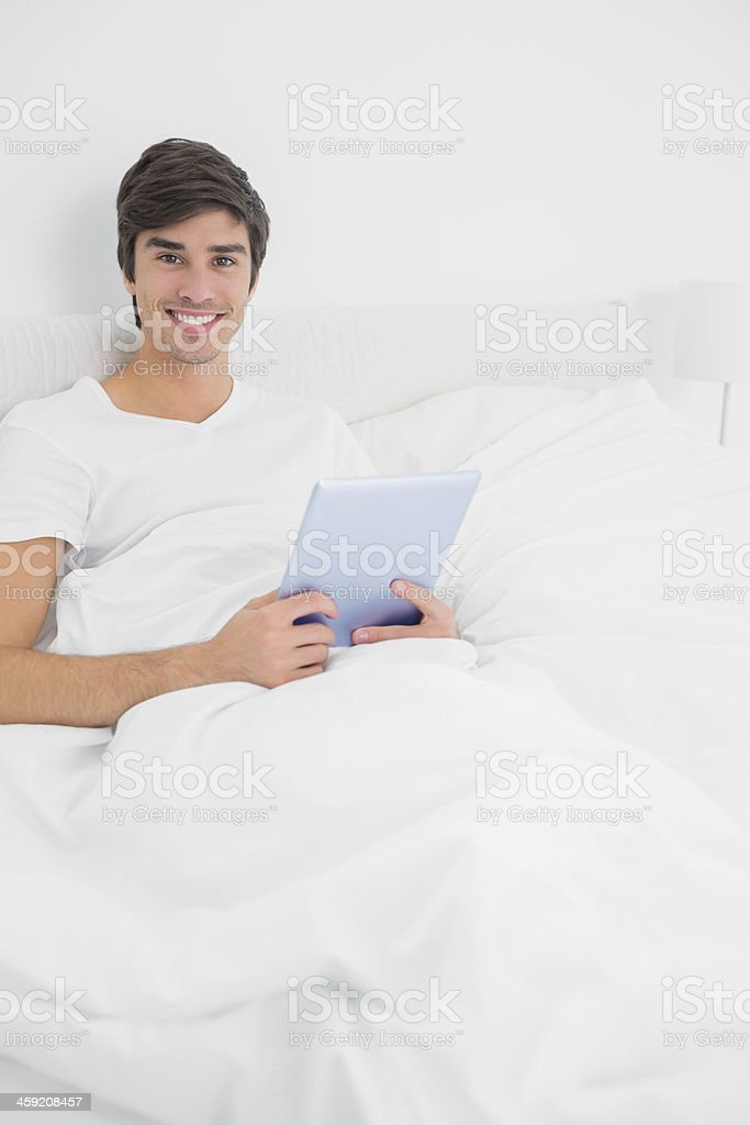 Happy young man sitting in bed using tablet pc royalty-free stock photo
