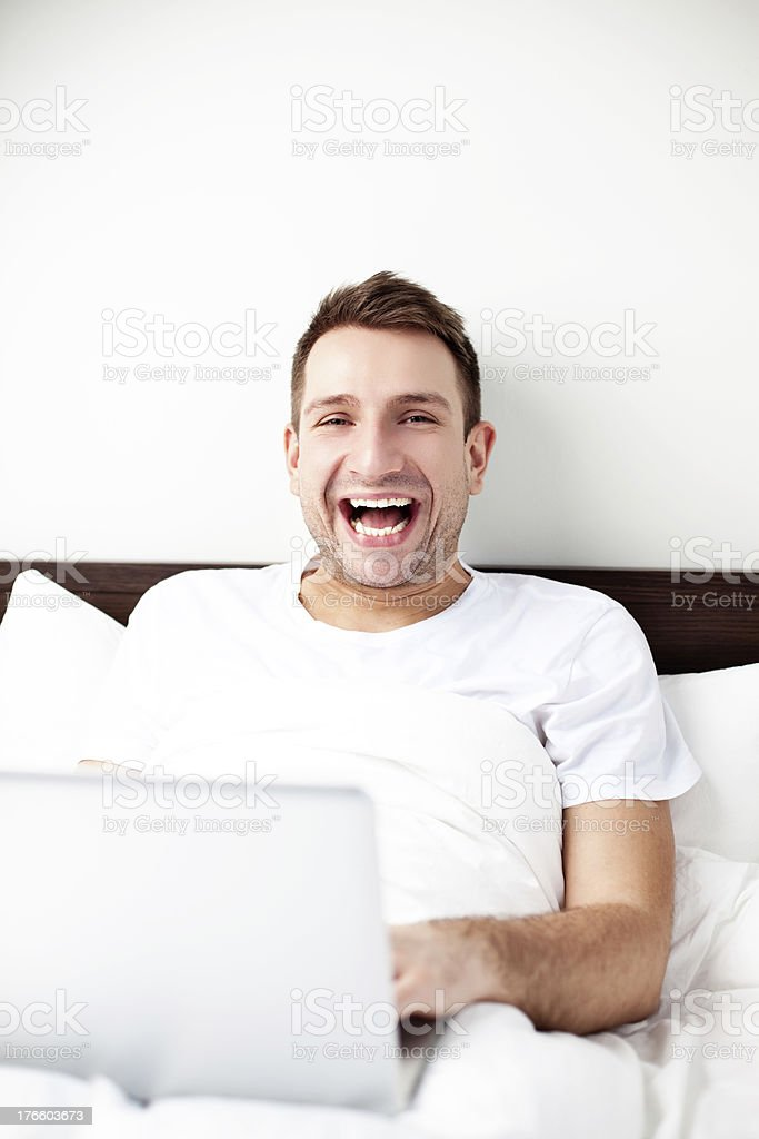 Happy young man sitting in bed with laptop stock photo