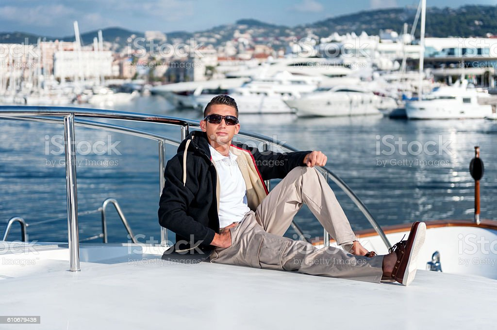 Happy young man sitting on yacht stock photo