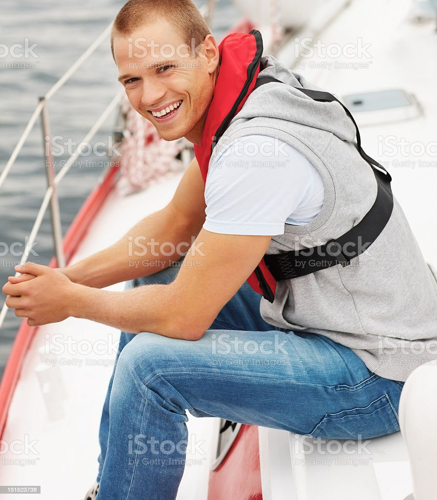 Happy young man smiling in a boat stock photo