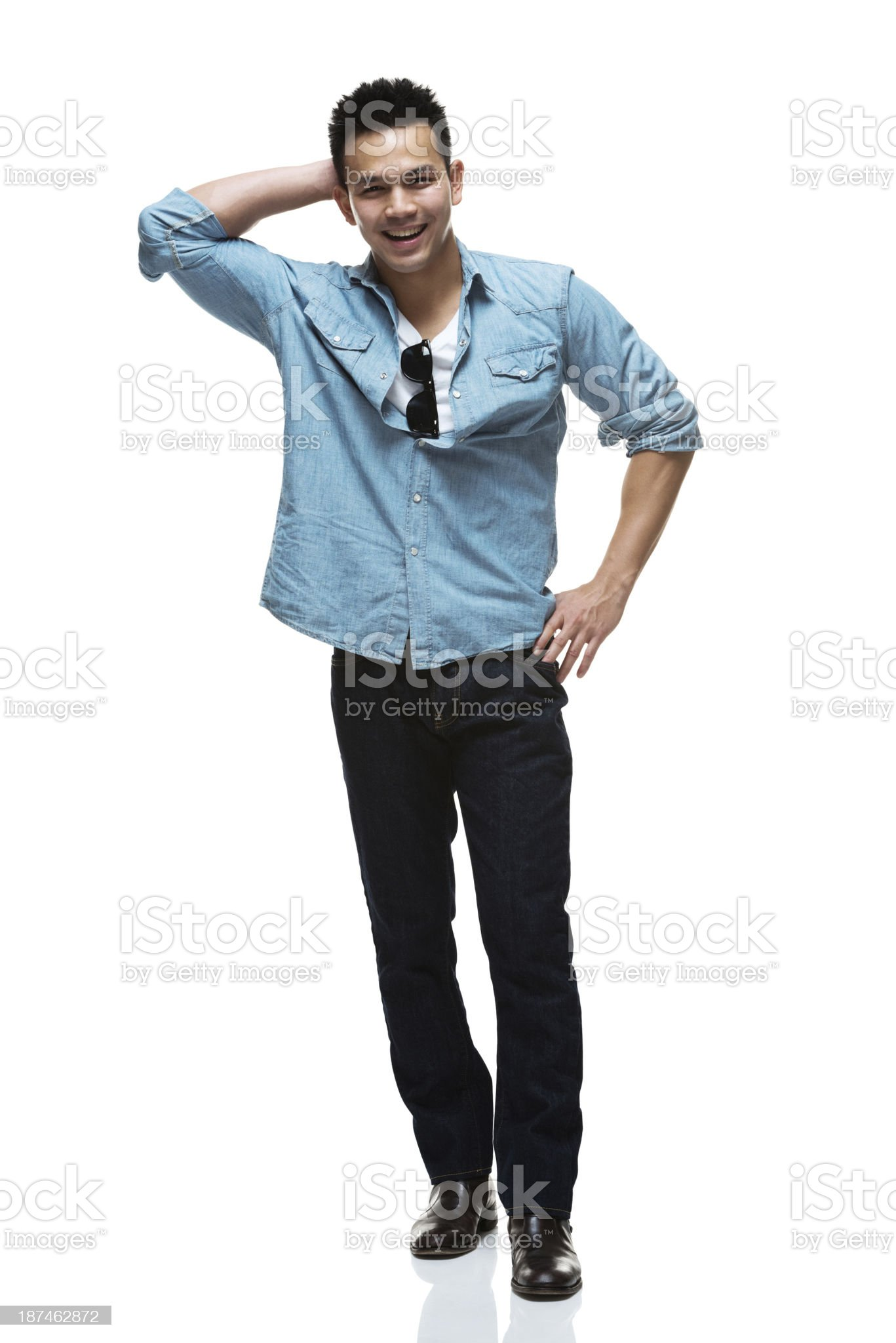 Happy young man standing with hand on hip royalty-free stock photo