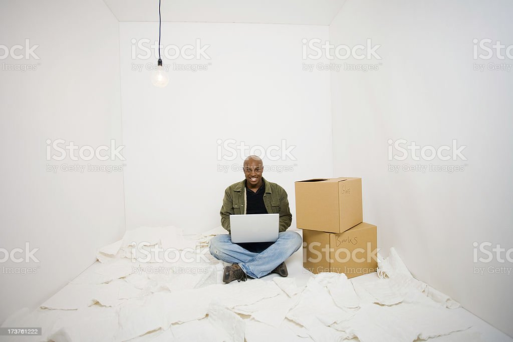 Happy young man surrounded by packing materials types on laptop royalty-free stock photo