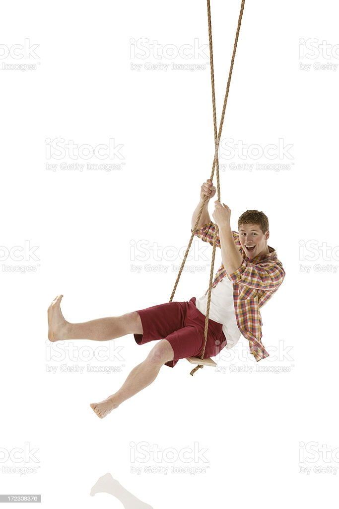 Happy young man swinging on a rope swing royalty-free stock photo