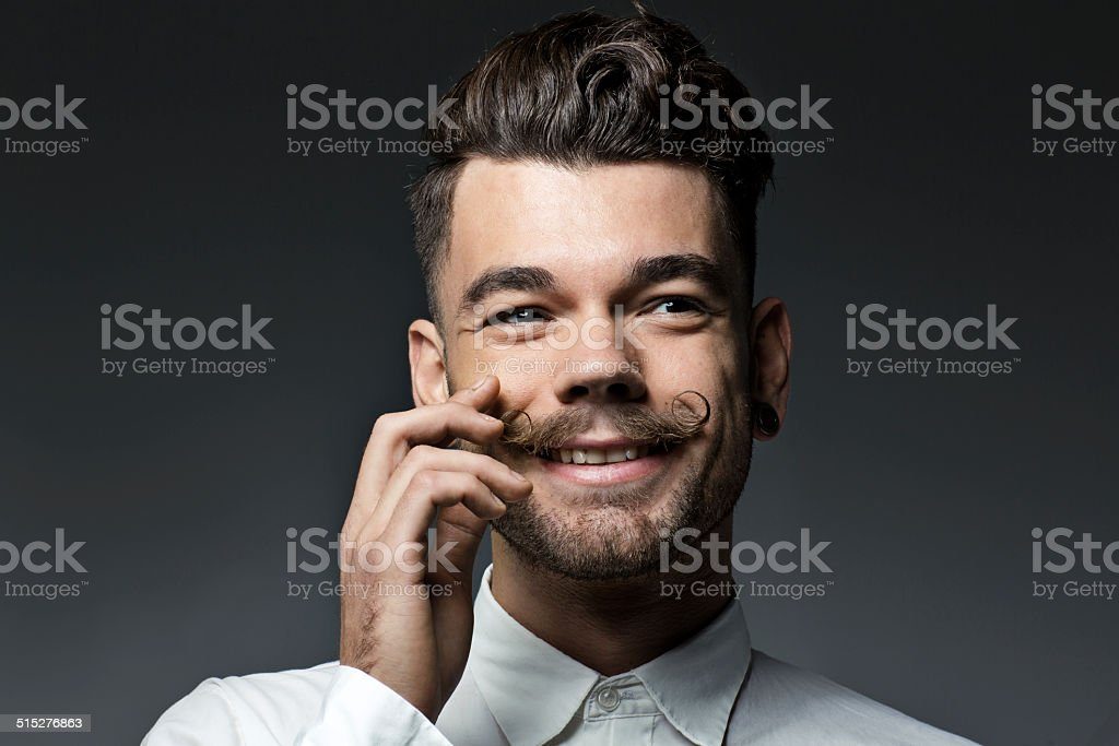 happy young man touching moustache stock photo