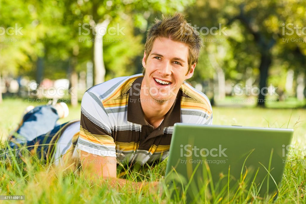 Happy young man using laptop at park royalty-free stock photo