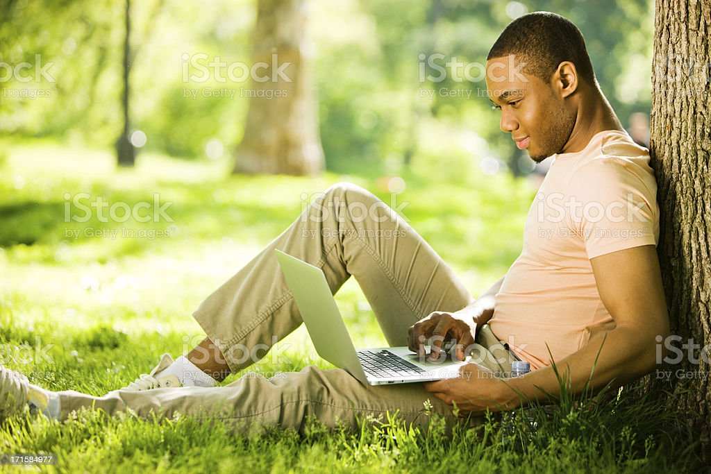 Happy Young Man using laptop in park stock photo