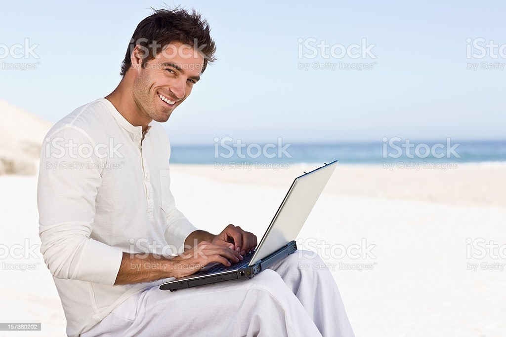 Happy young man using laptop on beach royalty-free stock photo
