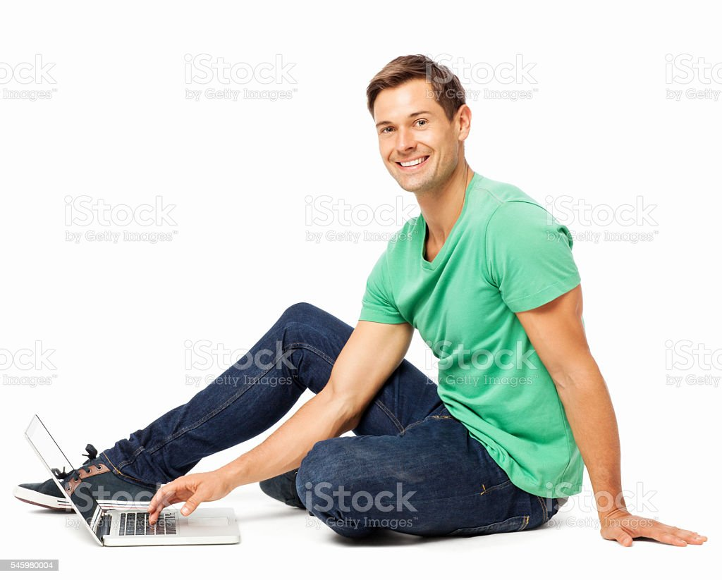 Happy Young Man Using Laptop On Floor stock photo