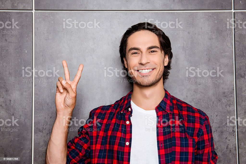 Happy young man  with beaming smile showing two fingers stock photo