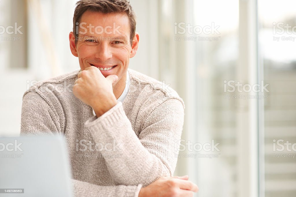 Happy young man with hand on chin royalty-free stock photo