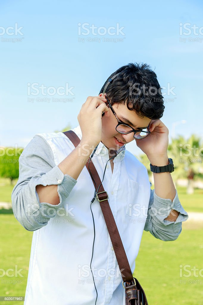 Happy young man with headphones and smiling ,outdoors. stock photo