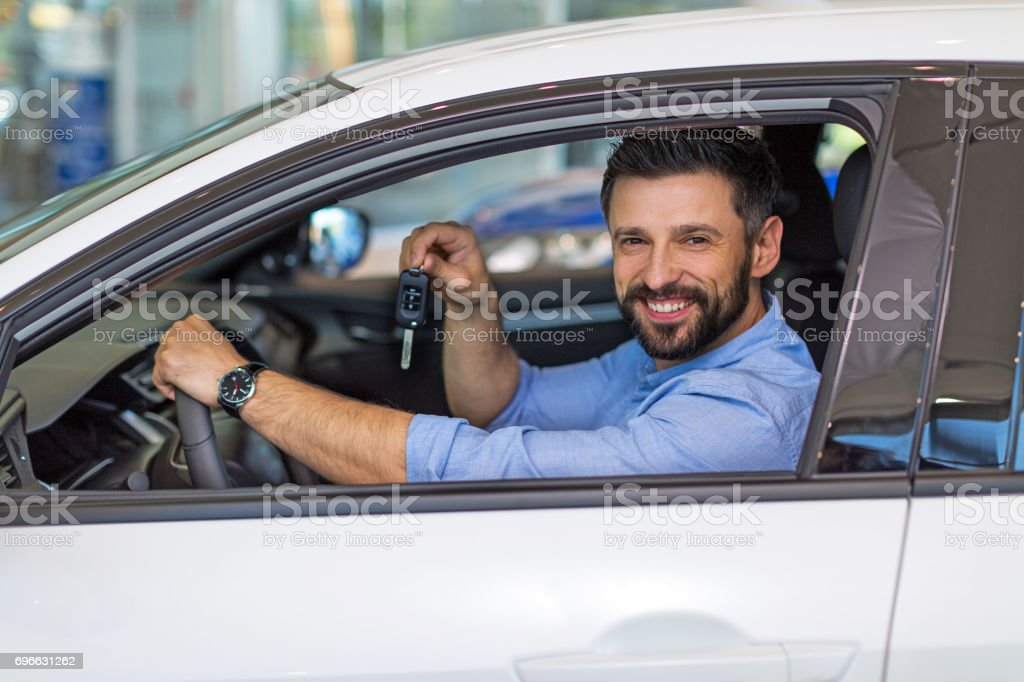 Happy young man with his new car stock photo