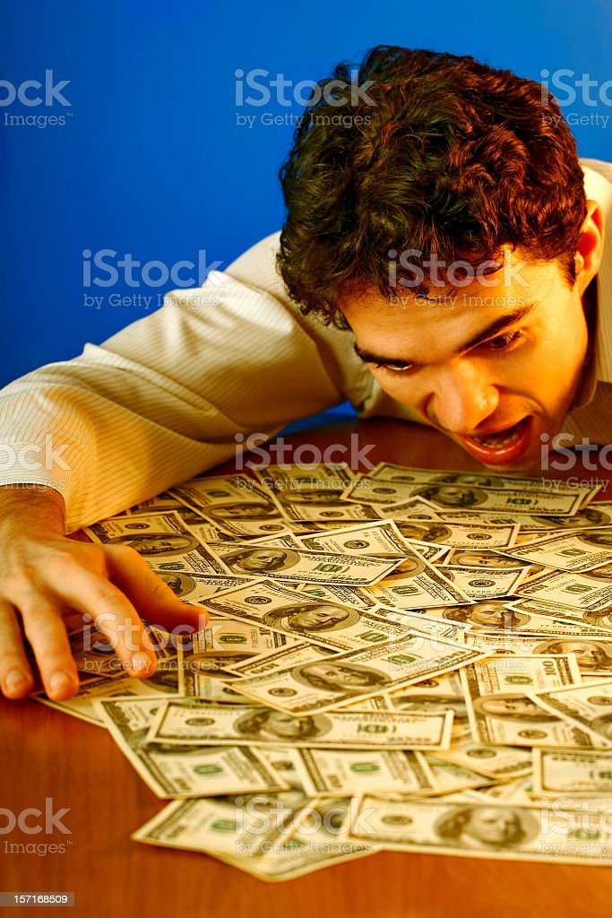 Happy young man with lots of US dollars royalty-free stock photo
