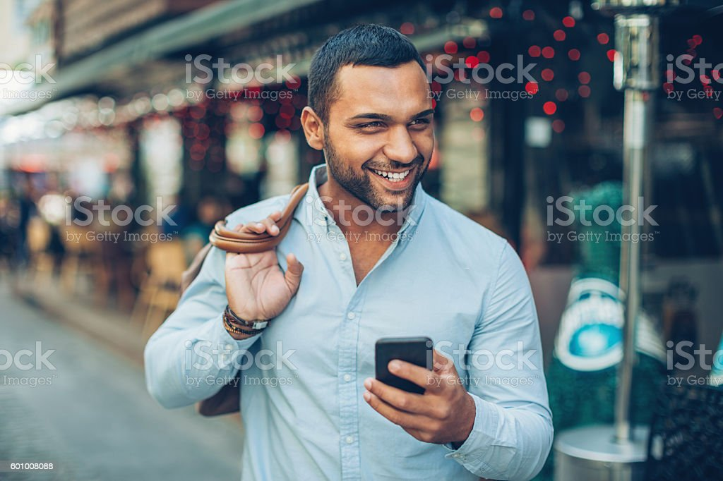Happy young man with mobile phone stock photo