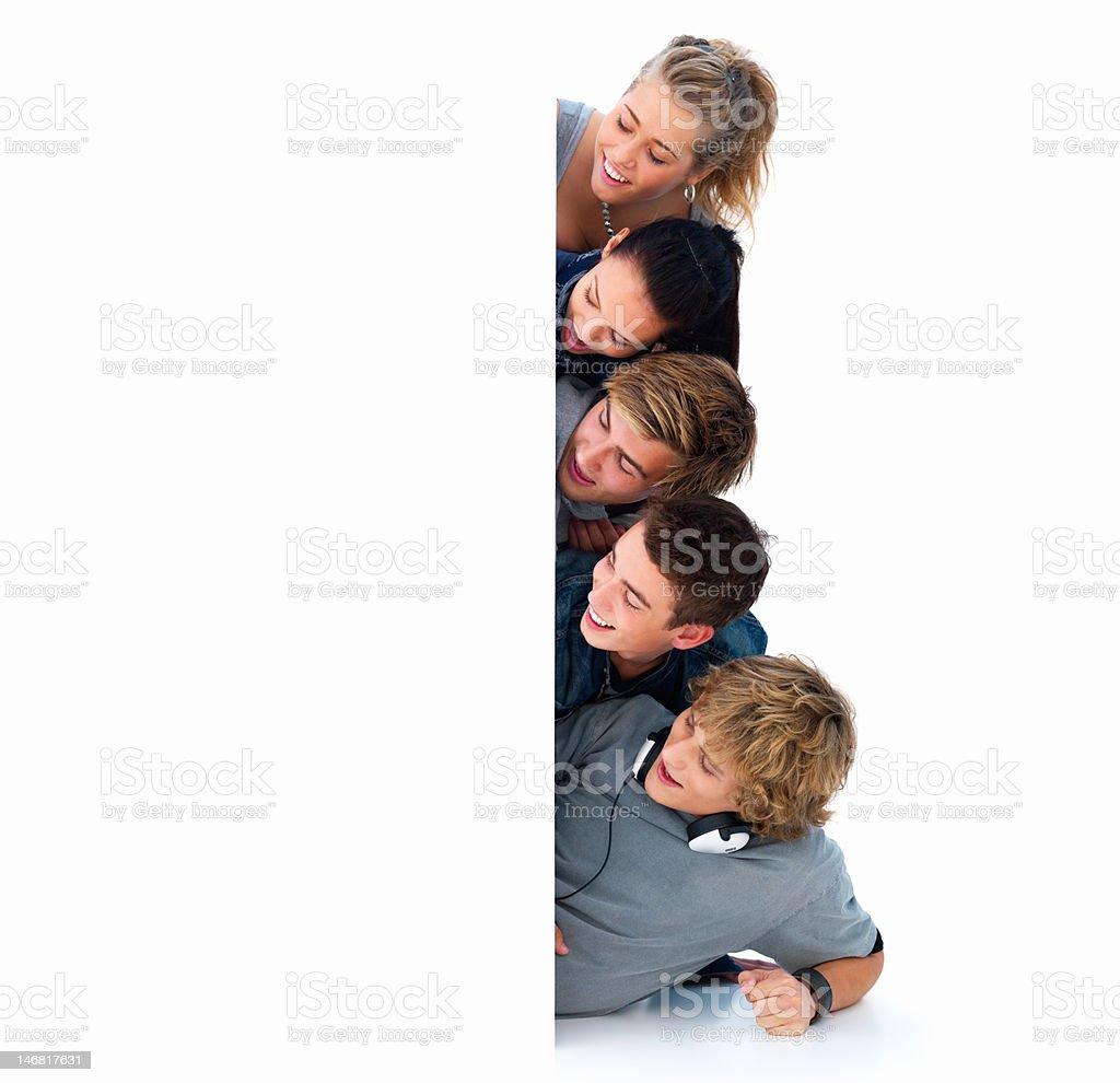 Happy young men and women peeking through white placard royalty-free stock photo