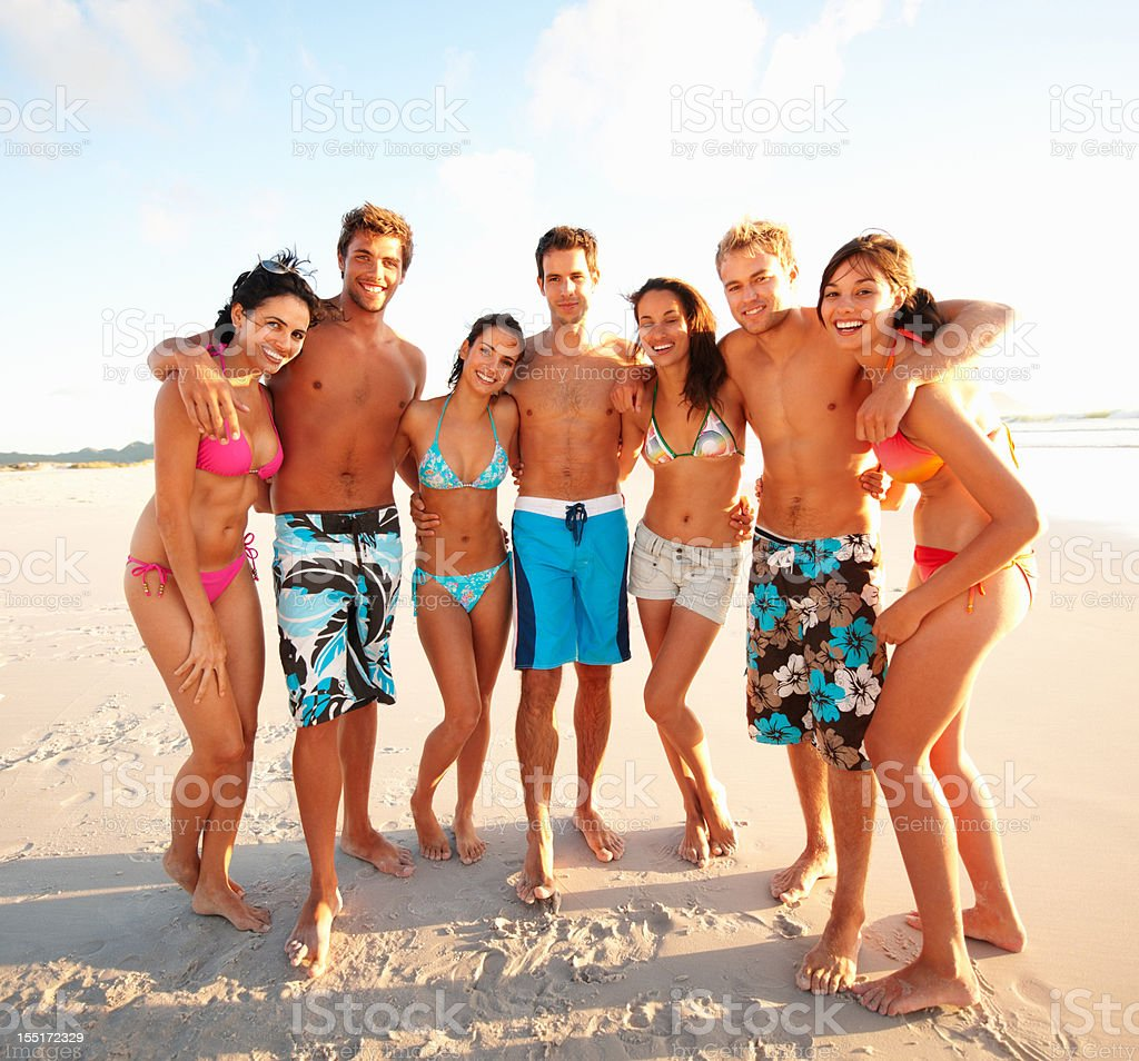 Happy young men and women standing on beach royalty-free stock photo