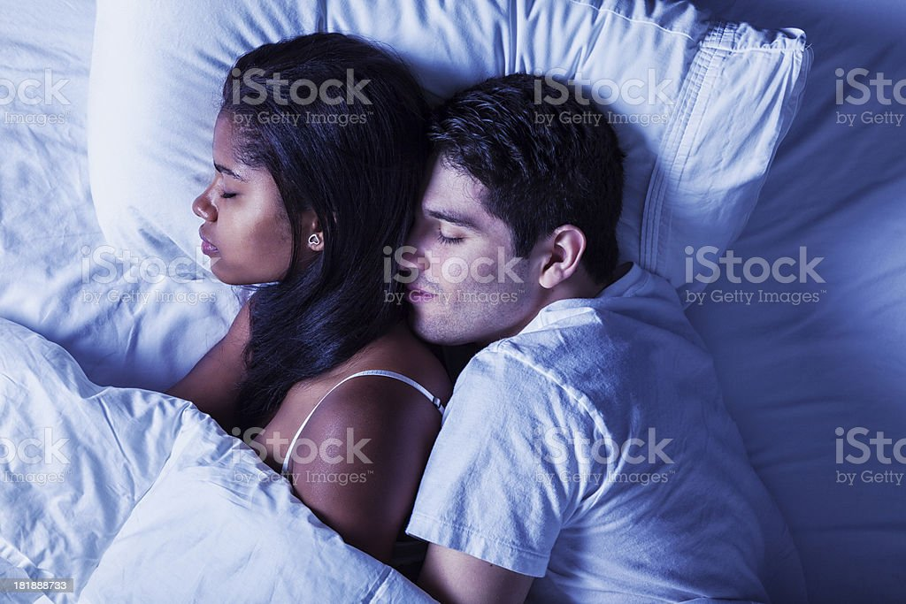 Happy Young Mixed-race Couple Sleeping in Bed stock photo