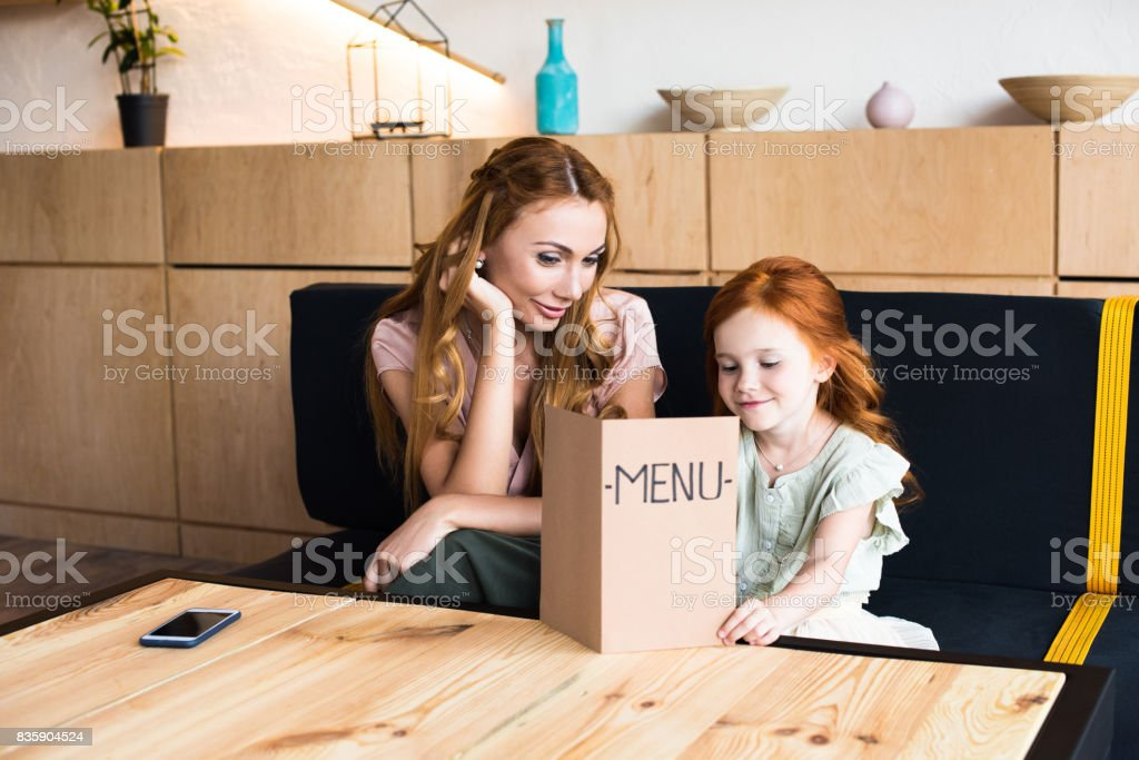 happy young mother and adorable redhead daughter reading menu in cafe stock photo