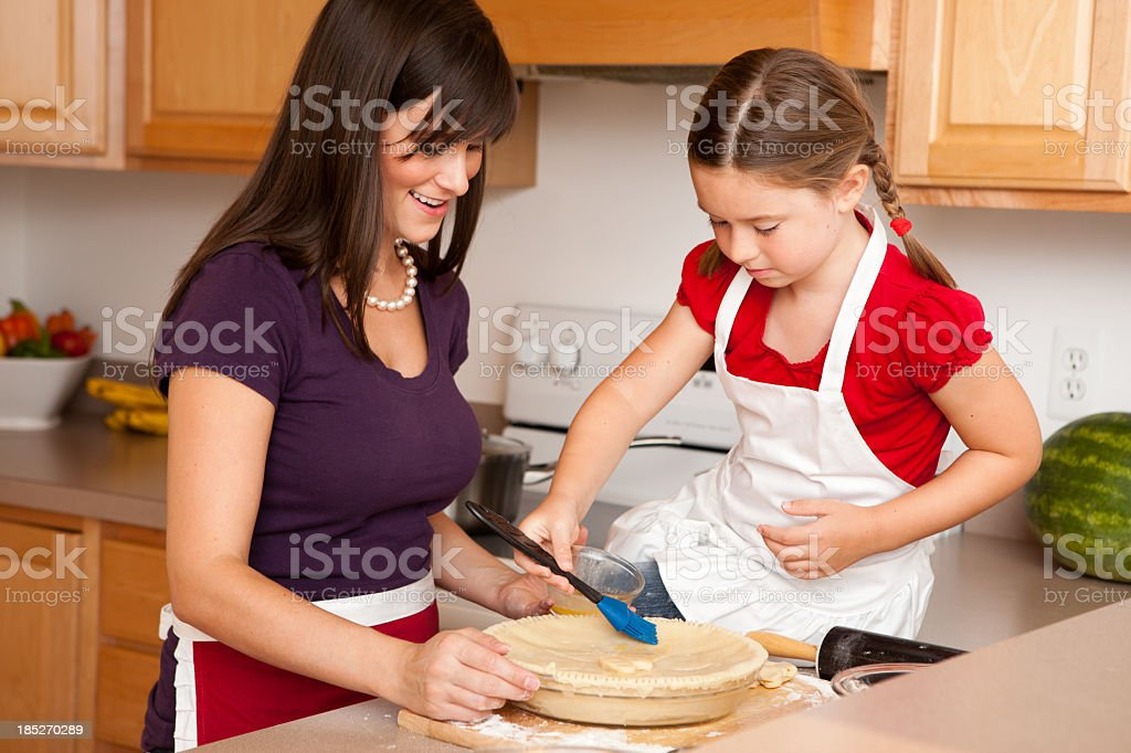 Happy Young Mother and Her Daughter Baking Pie in Kitchen royalty-free stock photo