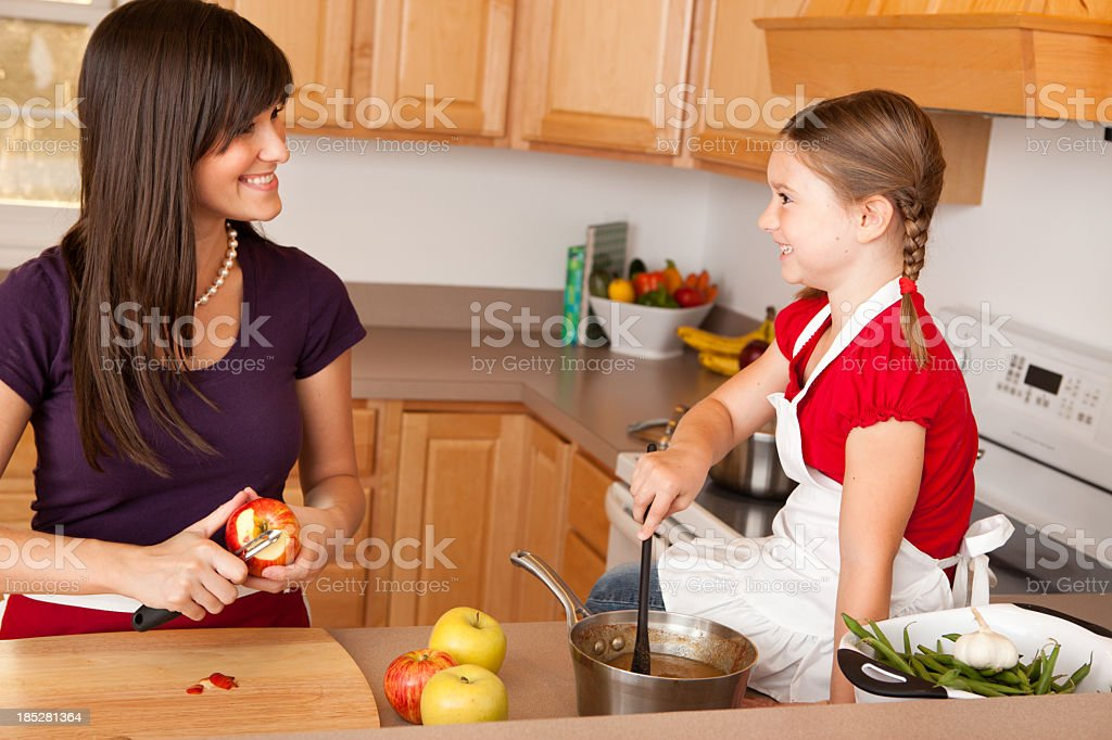 Happy Young Mother and Her Daughter Cooking Together in Kitchen royalty-free stock photo