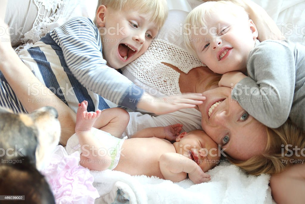 Happy Young Mother and Three Children Snuggling on Bed stock photo