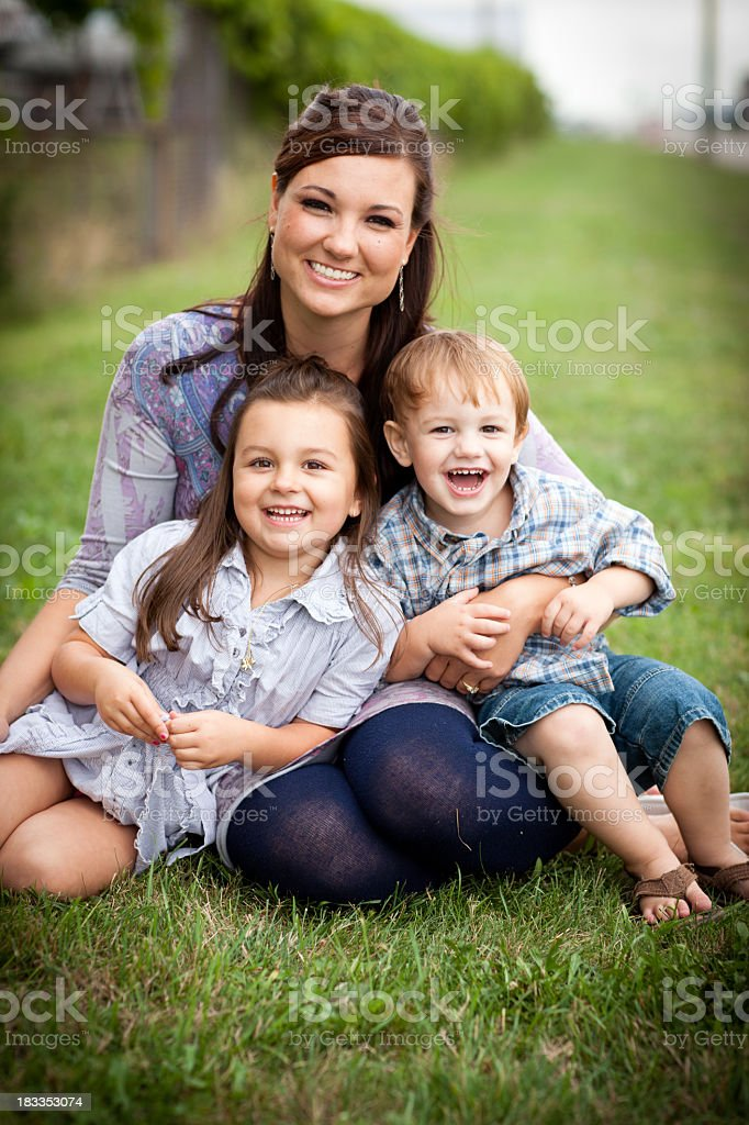 Happy Young Mother, Daughter and Son Sitting Together Outside stock photo