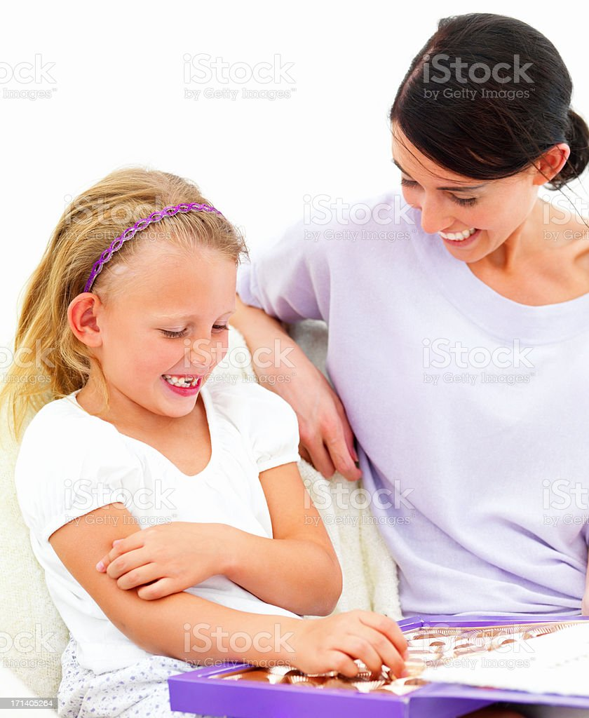 Happy young mother with daughter sitting together with chocolates stock photo