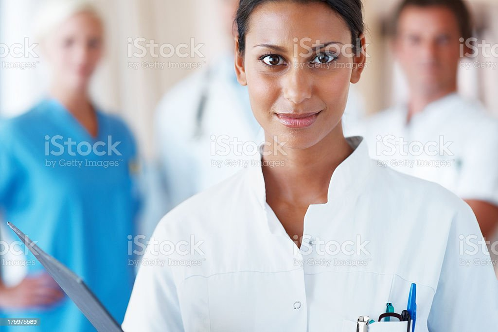Happy young nurse with her team standing behind stock photo
