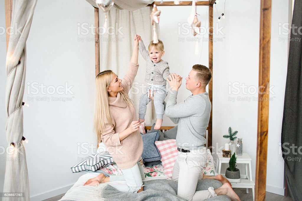 Happy young parents with baby boy in christams decorated room stock photo