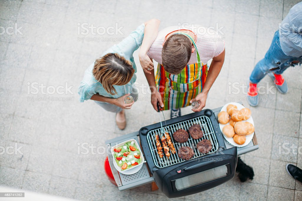 Happy Young People Barbecue At Patio. stock photo