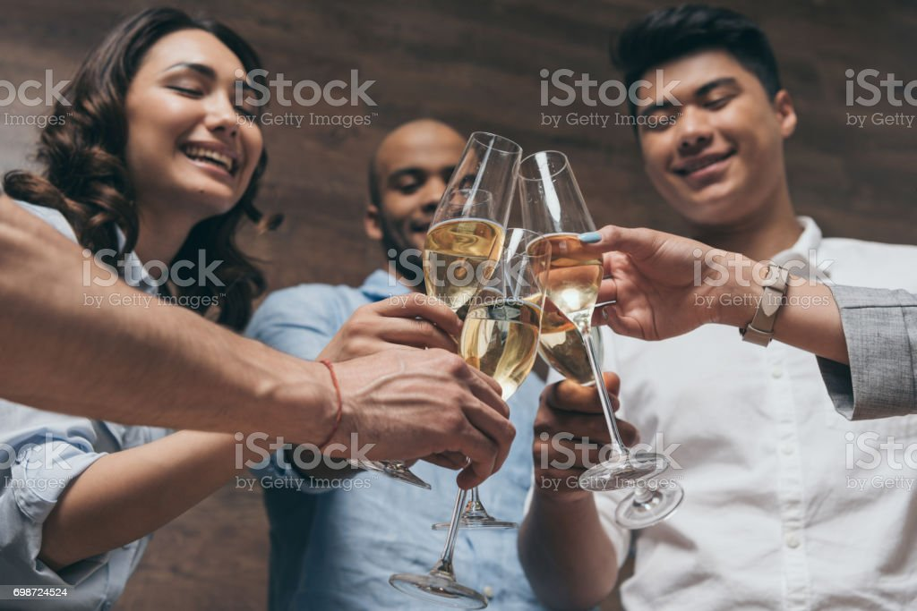 Happy young people clinking glasses of champagne during celebration stock photo