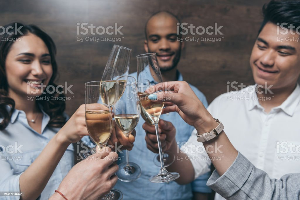 Happy young people clinking glasses of champagne indoors stock photo