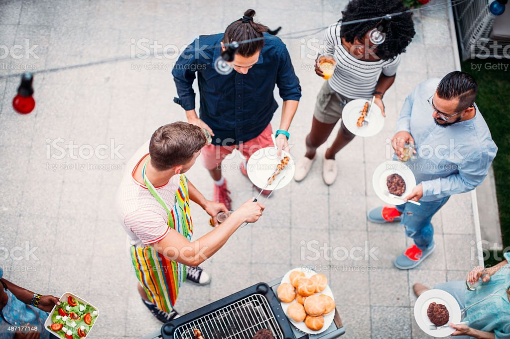Happy Young People Eating At Barbecue Party. stock photo