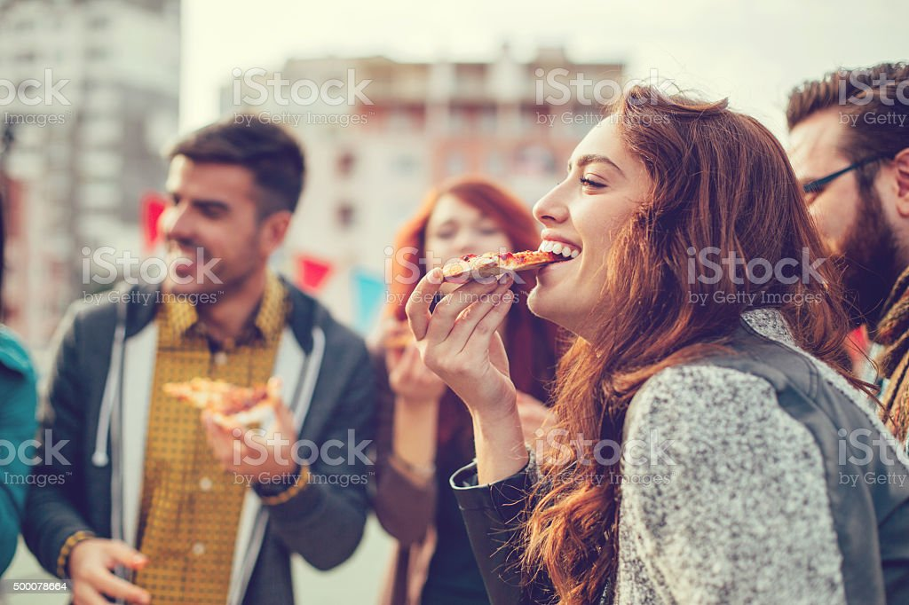 Happy young people eating pizza outdoors stock photo
