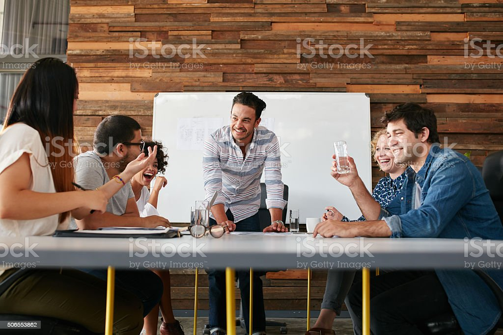 Happy young people having a business meeting stock photo