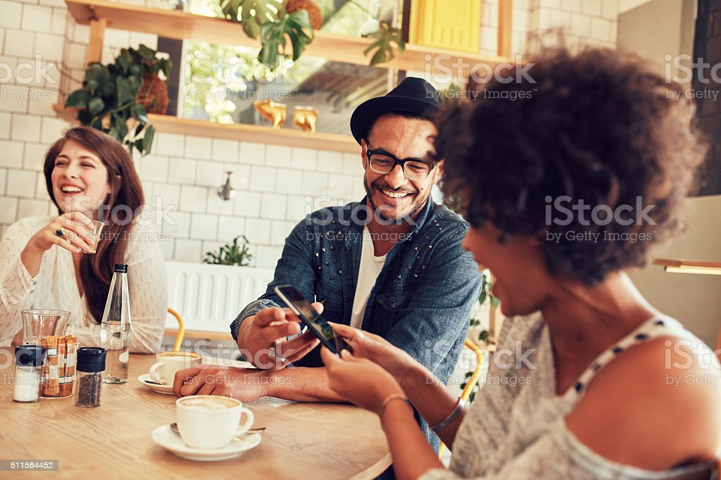 Happy young people having a great time at restaurant stock photo
