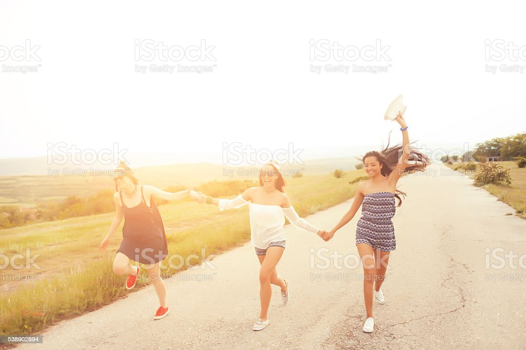 Happy young people holding hands and dancing on the road stock photo